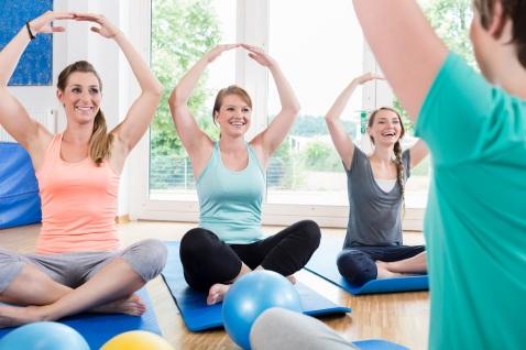 Moms in postnatal regression course doing yoga